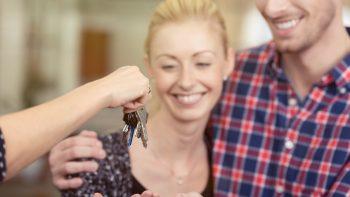 lachendes paar erhält die schlüssel zur wohnung